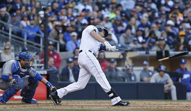 San Diego Padres' Seth Smith has his bat snapped but manages to drive the ball into center field for a base hit in the sixth inning of baseball game against the Los Angeles Dodgers Tuesday, April 1, 2014, in San Diego. (AP Photo/Lenny Ignelzi)
