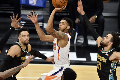 Phoenix Suns guard Cameron Payne (15) shoots between Memphis Grizzlies guards Dillon Brooks (24) and Tyus Jones (21)in the second half of an NBA basketball game Monday, Jan. 18, 2021, in Memphis, Tenn. (AP Photo/Brandon Dill)