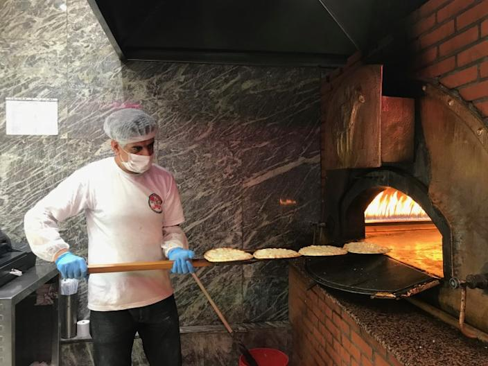 """A worker tends to a fire-brick oven while making manousheh, a Lebanese flatbread pizza. <span class=""""copyright"""">(Nabih Bulos / Los Angeles Times)</span>"""