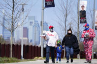 Fans walk outside Citizens Bank Park before an opening day baseball game between the Philadelphia Phillies and the Atlanta Braves, Thursday, April 1, 2021, in Philadelphia. The U.S. moved closer Thursday toward vaccinating 100 million Americans in a race against an uptick in COVID-19 cases that is fueling fears of another nationwide surge just as the major league baseball season starts and thousands of fans return to stadiums. (AP Photo/Matt Slocum)