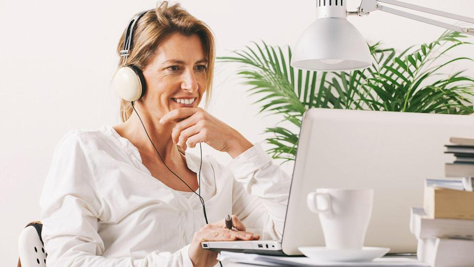 Smiling mature woman listening music with headphones.