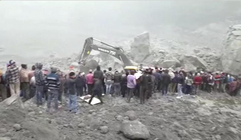 In this photo made from video, people watch an excavator dig into a collapsed mine, Friday, Dec. 30, 2016, in th Godda district, in eastern India. The coal mine collapsed late Thursday and could still have over a dozen miners trapped inside. (AP Photo)