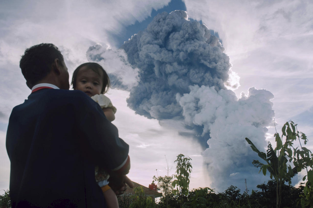 FILE - In this Sunday, June 9, 2019, file photo, a man carrying a child watches Mount Sinabung spew volcanic material into the air during an eruption, in Kabanjahe, North Sumatra, Indonesia. On Friday, June 14, 2019, The Associated Press reported on an educational simulation video made with 3D technology seven years ago that recent online posts have incorrectly identified as footage from the eruption. (AP Photo)