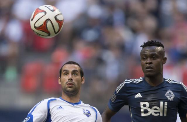 Montreal Impact's Andres Romero, left, chases down the ball while being watched by Vancouver Whitecaps' Gershon Koffie during the first half of an MLS soccer game Wednesday, June 25, 2014, in Vancouver, British Columbia. (AP Photo/The Canadian Press, Darryl Dyck)