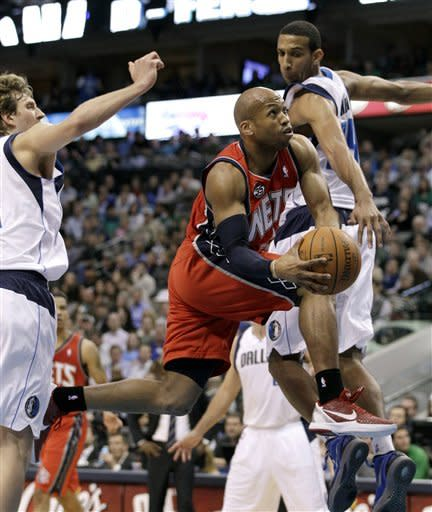 New Jersey Nets' Sundiata Gaines, center, gets by Dallas Mavericks defenders Dirk Nowitzki, left, of Germany, and Brandan Wright, right, in the first half of an NBA basketball game, Tuesday, Feb. 28, 2012, in Dallas. (AP Photo/Tony Gutierrez)