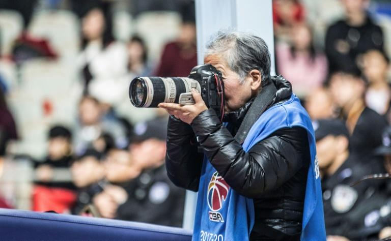 Photographer Hong Nanli, 79, in action taking pictures during a basketball match in Shanghai