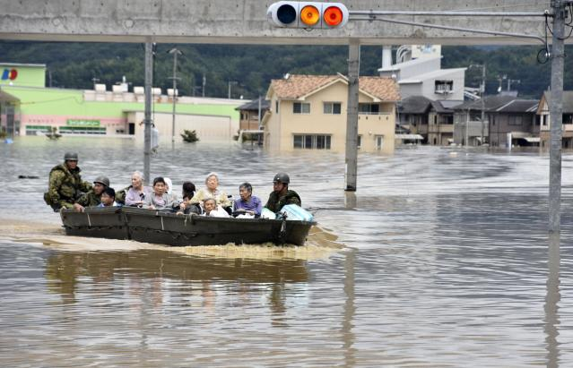 <p>Elderly people are rescued on boat as the city is flooded following heavy rain in Kurashiki city, Okayama prefecture, southwestern Japan, July 8, 2018. Heavy rainfall hammered southern Japan for the third day, prompting new disaster warnings on Kyushu and Shikoku islands on Sunday. (Photo: Kyodo News via AP) </p>