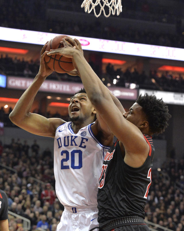 Louisville center Steven Enoch (23) attempts to block the shot of Duke center Marques Bolden (20) during the first half of an NCAA college basketball game in Louisville, Ky., Tuesday, Feb. 12, 2019. (AP Photo/Timothy D. Easley)
