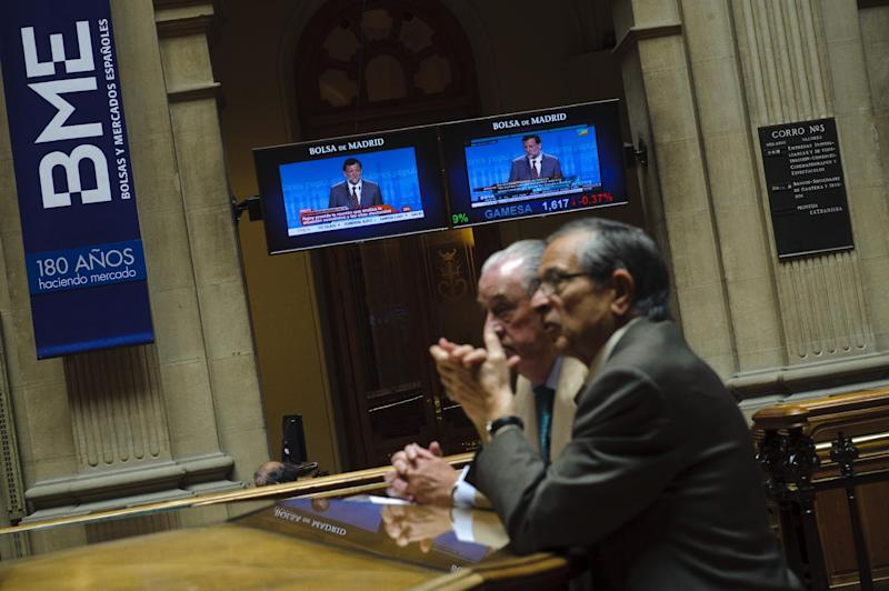 Brokers talk, while screens display Spain's Prime Minister Mariano Rajoy speech, at the Stock Exchange in Madrid, Monday, May 28, 2012. Shares in Spanish bank Bankia, one of the banks hardest hit by Spain's real estate collapse over the past four years, fell 28 per cent on opening in Madrid on Monday, the bank's first day back on the stock exchange following its announcement Friday that it would need Euro 19 billion ($23.8 billion) bailout to bolster its defenses.(AP Photo/Daniel Ochoa de Olza)
