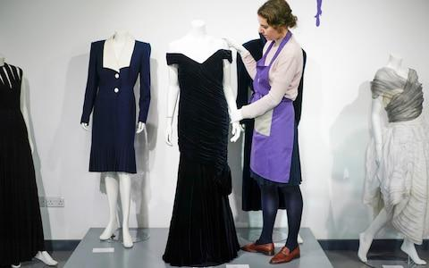 An assistant poses with Princess Diana's Victor Edelstein midnight-blue velvet evening gown - Credit: Reuters