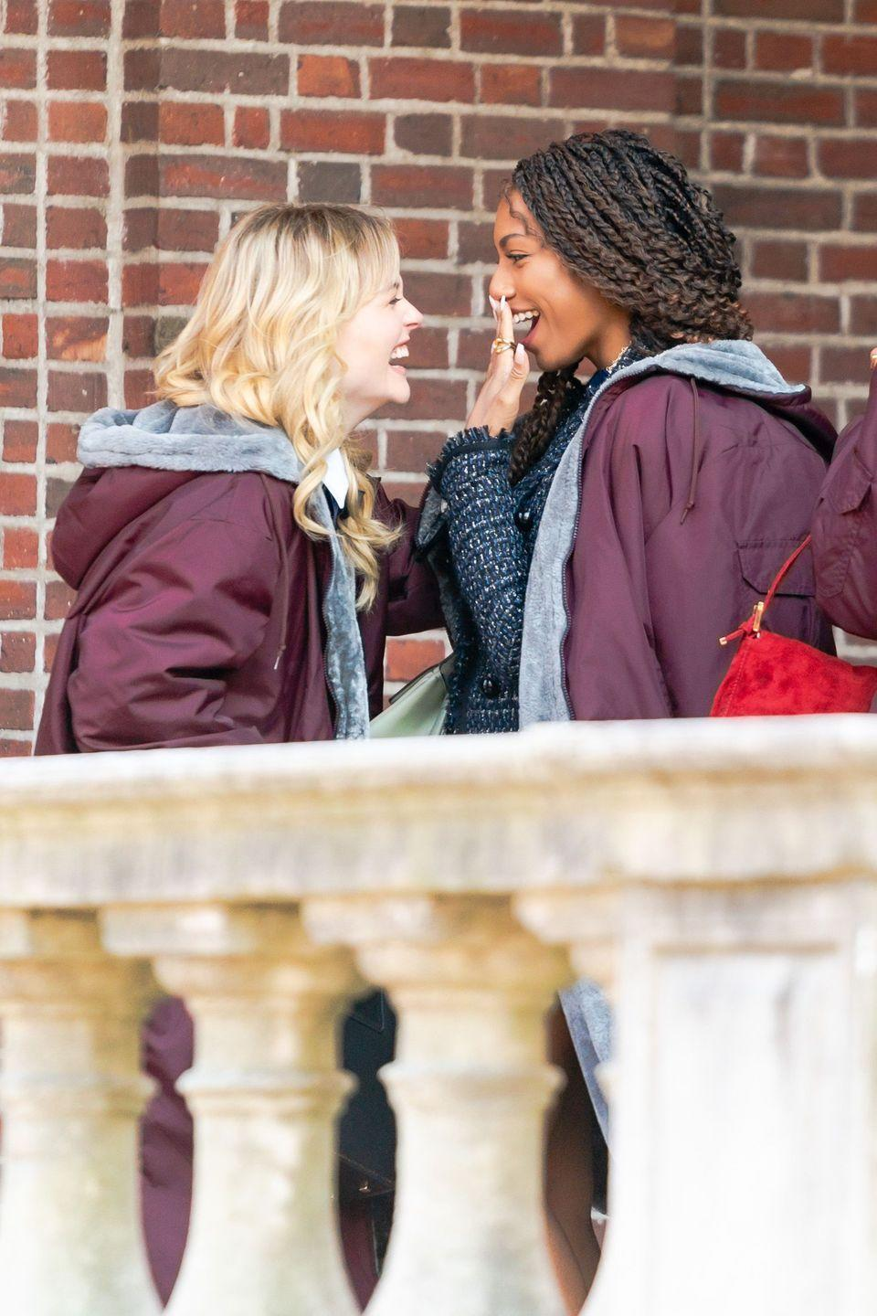<p>Emily Alyn Lind and Savannah Smith, keeping warm under thick coats between takes, laugh it out on set. </p>