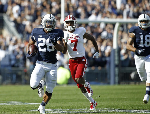 """Penn State's <a class=""""link rapid-noclick-resp"""" href=""""/ncaaf/players/256698/"""" data-ylk=""""slk:Saquon Barkley"""">Saquon Barkley</a> (26) takes the opening kick off 98 yards for a touchdown against Indiana during the first half of an NCAA college football game in State College, Pa., Saturday, Sept. 30, 2017. (AP Photo/Chris Knight)"""