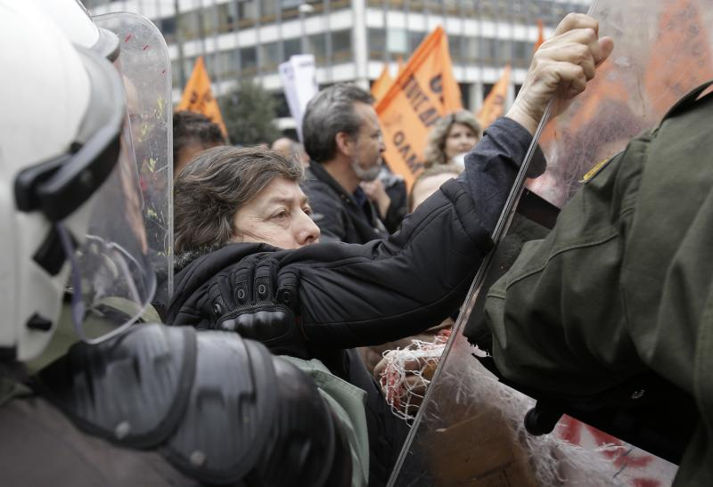 A protesting woman holds the shield of a riot policeman as another one pushes her, outside the Finance Ministry during a rally in Athens, on Friday, Feb. 28, 2014. Some hundreds of teachers, municipality workers, school guards and cleaning women who have been suspended on reduced pay pending transfer to other public sector jobs or dismissal, took part in the protest as the officials from the European Union, European Central Bank and International Monetary Fund, together known as the troika, were holding talks with the Minister of Administration Reform Kyriakos Mitsotakis and other government officials. (AP Photo/Thanassis Stavrakis)