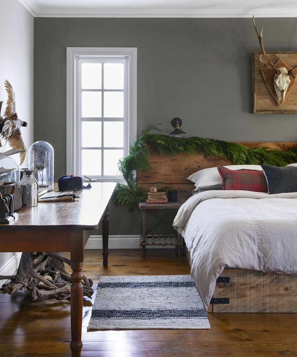 """<p>An oversized garland draped across a headboard adds some Christmas cheer without going overboard. Swap out accent pillows for plaid ones to up the ante. </p><p><a class=""""link rapid-noclick-resp"""" href=""""https://www.amazon.com/slp/decorative-garland/njqpwobgftvd7ed?tag=syn-yahoo-20&ascsubtag=%5Bartid%7C10050.g.1247%5Bsrc%7Cyahoo-us"""" rel=""""nofollow noopener"""" target=""""_blank"""" data-ylk=""""slk:SHOP GARLAND"""">SHOP GARLAND</a></p>"""