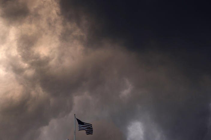 FILE - In this March 19, 2020, file photo, an American flag is dwarfed by storm clouds as they pass over a downtown Kansas City, Mo. (AP Photo/Charlie Riedel, File)