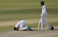 Pakistan's Fawad Alam, center, prostrates after scoring century while his teammate Faheem Ashraf watches during the second day of the first cricket test match between Pakistan and South Africa at the National Stadium, in Karachi, Pakistan, Wednesday, Jan. 27, 2021. (AP Photo/Anjum Naveed)