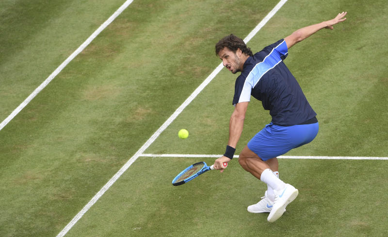 Feliciano Lopez returns the ball to Gilles Simon during their match at the ATP Mercedes Cup tournament in Stuttgart, Thursday, June 14, 2018 in Aktion. (Marijan Murat/dpa via AP)
