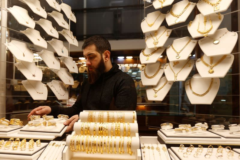 A salesman arranges gold bracelets inside a jewellery shop in Beirut