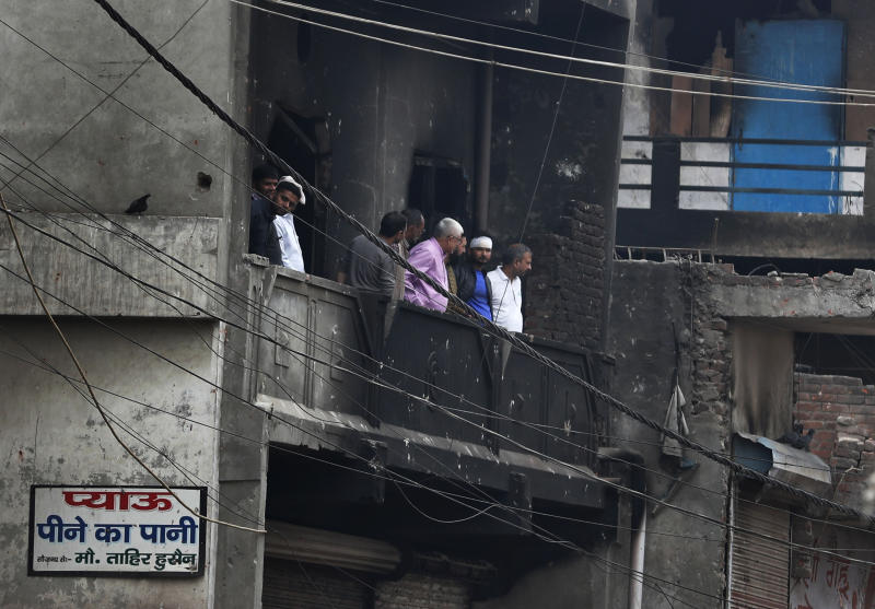 """Residents of a burnt building assess the damage following Tuesday's violence in New Delhi, India, Thursday, Feb. 27, 2020. India accused a U.S. government commission of politicizing communal violence in New Delhi that killed at least 30 people and injured more than 200 as President Donald Trump was visiting the country. The violent clashes between Hindu and Muslim mobs were the capital's worst communal riots in decades and saw shops, Muslim shrines and public vehicles go up in flames. Signage in Hindi reads, """"Drinking Water"""".(AP Photo/Rajesh Kumar Singh)"""