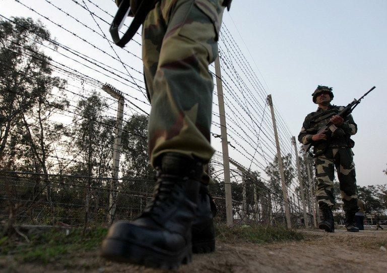 Indian soldiers patrol along the border fence with Pakistan at Suchet Garh, about 36 kms from Jammu, on January 16, 2013