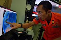 An official from Indonesia's national search and rescue agency in Medan points at his computer screen to the position where AirAsia flight QZ8501 went missing, December 28, 2014