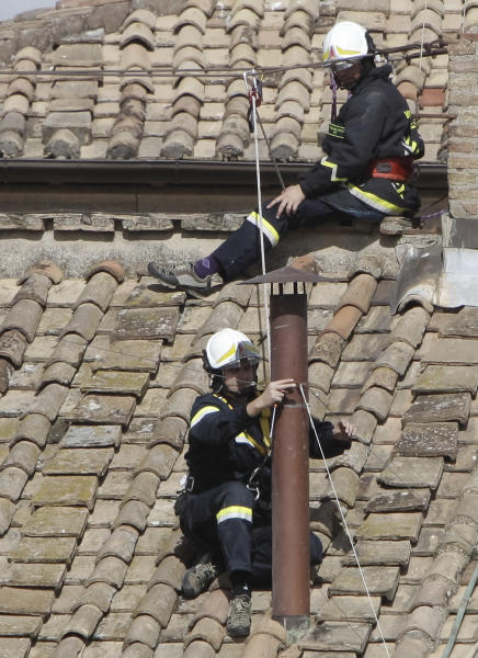 Firefighters place the chimney on the roof of the Sistine Chapel, where cardinals will gather to elect the new pope, at the Vatican, Saturday, March 9, 2013. The preliminaries over, Catholic cardinals are ready to get down to the real business of choosing a pope. And even without a front-runner, there are indications they will go into the conclave Tuesday with a good idea of their top picks. The conclave date was set Friday during a vote by the College of Cardinals, who have been meeting all week to discuss the church's problems and priorities, and the qualities the successor to Pope Benedict XVI must possess. (AP Photo/Stringer)