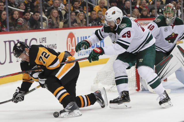 Pittsburgh Penguins' Patric Hornqvist (72) and Minnesota Wild's Greg Pateryn go for the puck during the second period of an NHL hockey game Thursday, Dec. 20, 2018, in Pittsburgh. (AP Photo/Keith Srakocic)