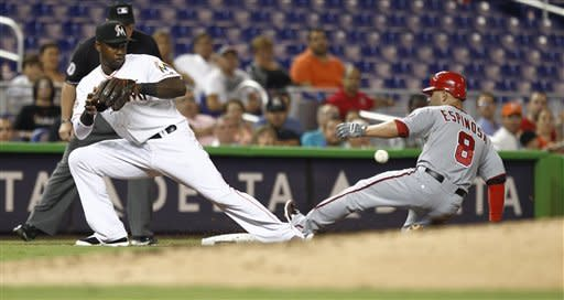 Washington Nationals runner Danny Espinosa (8) slides into third safe on a second inning triple and a late throw to Miami Marlins' Hanley Ramirez (2) during a baseball game in Miami, Monday, July 16, 2012. (AP Photo/J Pat Carter)