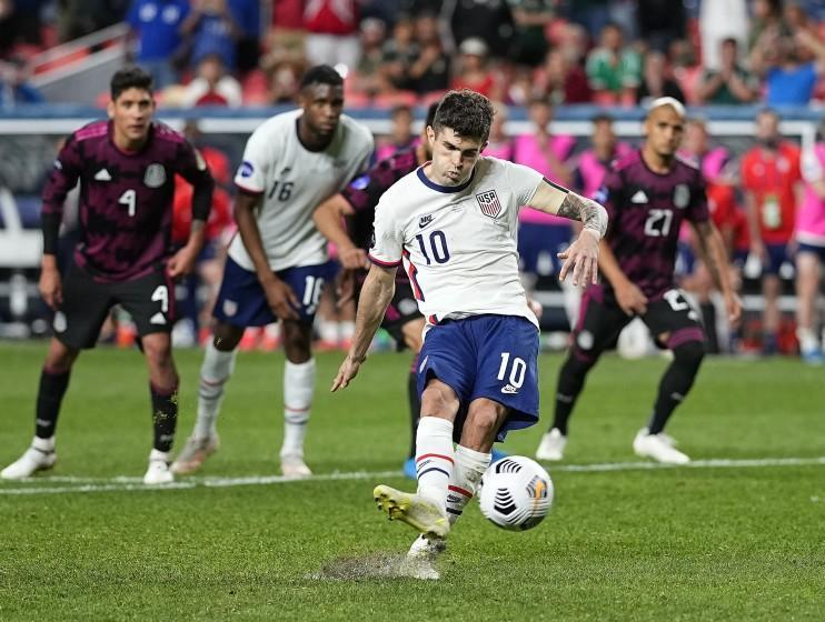 FILE - In this June 6, 2021, file photo, United States' Christian Pulisic (10) kicks a penalty kick for a goal against Mexico during extra time in the CONCACAF Nations League championship soccer match in Denver. Pulisic's availability for the United States' opening World Cup qualifier remains unclear following his positive COVID test. The top American player was on the 26-man roster announced Thursday for the first three qualifiers after missing Chelsea's match at Arsenal last weekend. The U.S. starts at El Salvador on Sept. 2. (AP Photo/Jack Dempsey, File)
