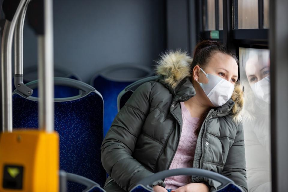 woman with face mask looking out the window on a bus