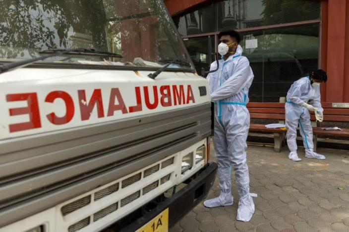 Health workers wear personal protective equipment (PPE) as they prepare to carry the body of a person, who died from complications related to the coronavirus disease (COVID-19), for cremation at a crematorium in New Delhi