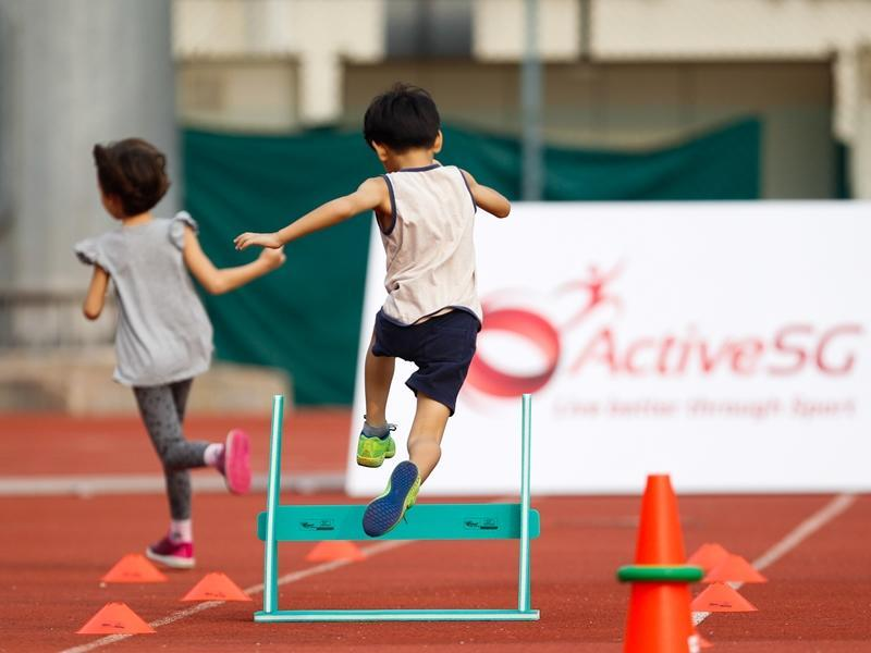 A shot of kids jumping over a hurdle