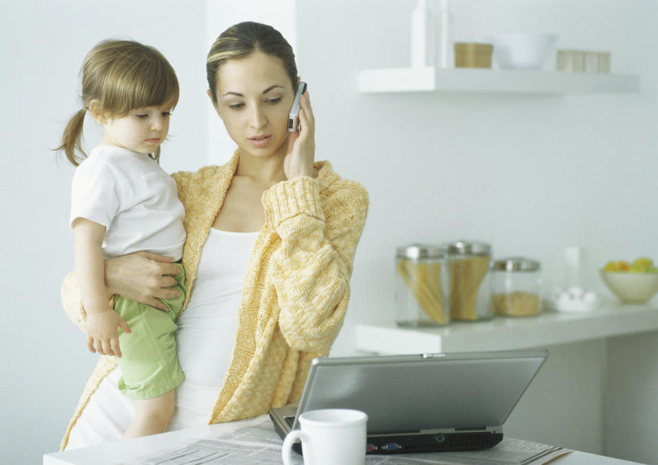 Woman looks furious on phone holding baby looking at laptop