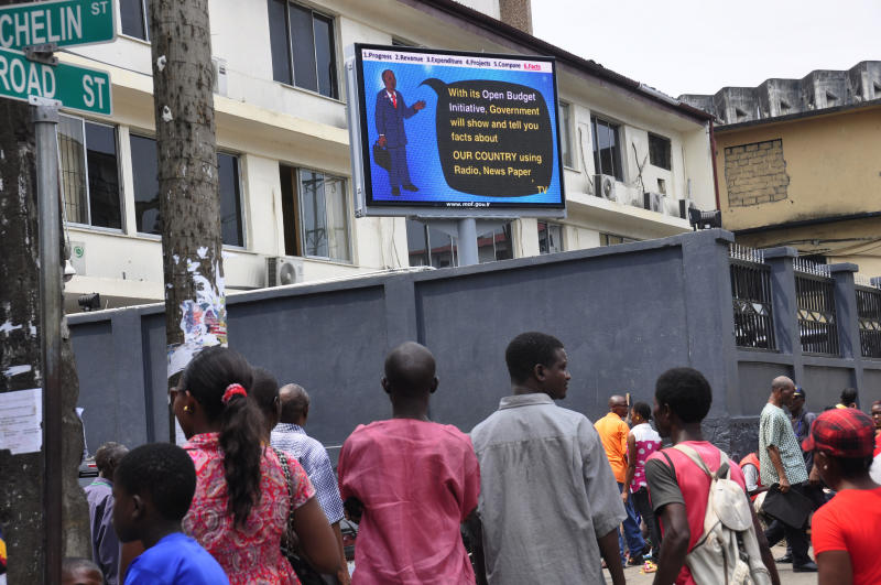 Passersby stop to look up at Liberia's new 'Open Budget Initiative' electronic billboard, located in a heavily trafficked area of Morovia, Liberia, Friday, Jan. 25, 2013. Liberia's government is sharing its financial outlook with the men and women on the street with a new electronic information billboard, switched on Wednesday, Jan. 23. The U.S.-supported project aims to improve state transparency. (AP Photo/Abbas Dulleh)