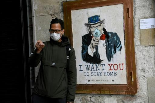 A man wearing a face mask poses with a poster by artist TVBoy in Barcelona, where authorities have ordered a widespread shop closure