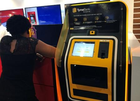 A woman stands next to a TymeBank client onboarding kiosk in Johannesburg