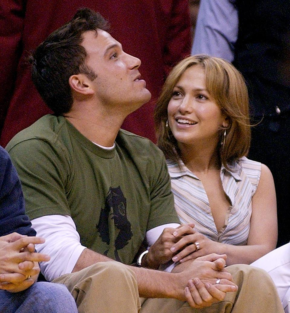 Ben Affleck and Jennifer Lopez sit together during Game 4 of the Western Conference Semifinals between the Los Angeles Lakers and the San Antonio Spurs, May 11, 2003, in Los Angeles. The couple split in 2004, but almost 17 years later rumors of their reunion have started to trend on social media.