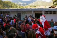Man dressed up as Santa Claus, hands out food to residents in a low-income neighbourhood in Guarenas