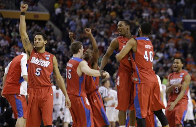 Dayton's Devin Oliver (5) celebrates with teammates during the second half of a third-round game against Syracuse in the NCAA men's college basketball tournament in Buffalo, N.Y., Saturday, March 22, 2014. Dayton won 55-53. (AP Photo/Frank Franklin II)