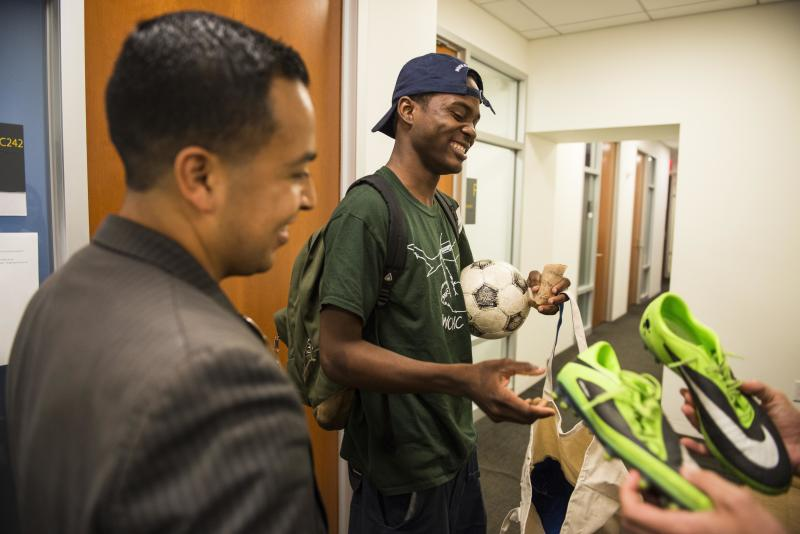 Attorney Cesar Vargas watches as his client Ivan Ruiz is given soccer shoes at the Safe Passage Project offices in Manhattan on Tuesday. (DAMON DAHLEN/HUFFPOST)
