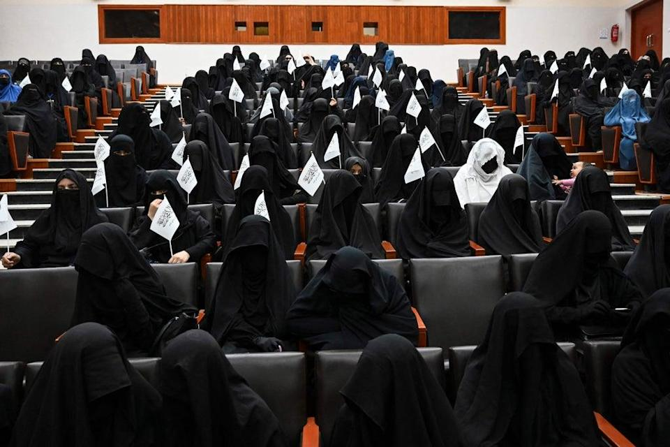 Veiled students hold Taliban flags as they listen a speaker before a pro-Taliban rally at the Shaheed Rabbani Education University in Kabul on September 11 (AFP via Getty Images)