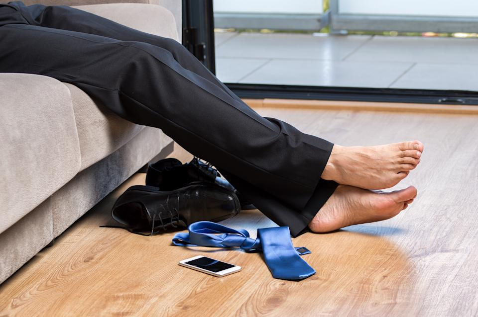 Profile of a tired businessman legs with black suit resting on couch at home after work with the blue tie and the phone on the floor