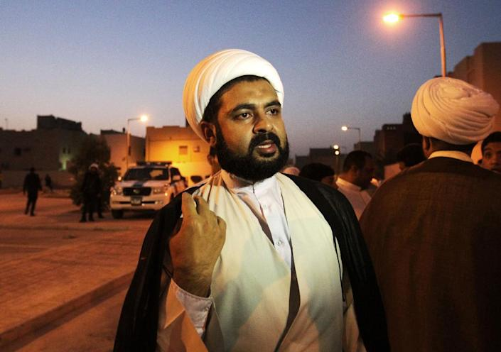 In this Saturday, June 22, 2013 photo, a Shiite cleric speaks with others as police block off a vacant lot, where a Shiite mosque stood until it was demolished during the crackdown that followed the Spring 2011 pro-democracy uprising in Nuwaidrat, Bahrain. Shiite worshipers often pray at the sites of demolished mosques, several of which people are rebuilding on their own, but were not allowed Saturday at the Nuwaidrat site after a confrontation earlier in the day. According to an opposition human rights activist, a hard-line Sunni Islamist member of parliament and his supporters arrived at the site to stop reconstruction work. Police blocked off the area. As evening prayer time approached, several Shiite clerics arrived to speak with police about allowing those gathered to pray at the site, but ended up urging people to go elsewhere to pray to avoid confrontation. (AP Photo/Hasan Jamali)