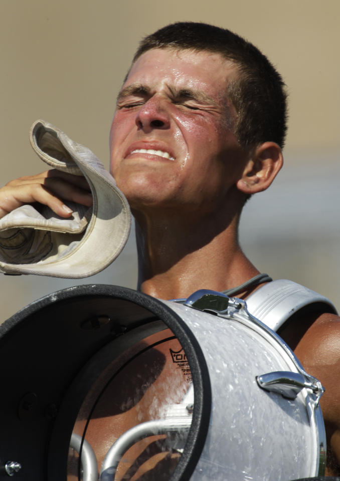 Alex Beltran, a drummer for The Cadets Drum and Bugle Corps from Allentown, Pa., looks for heat relief while practicing at Rose Hill High School in Rose Hill, Kan., Tuesday, July 19, 2011. The Corps is touring in an area that is under an excessive heat warning. (AP Photo/Orlin Wagner)