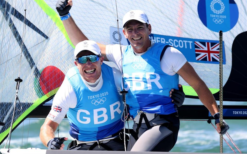 Dylan Fletcher and Stuart Bithell of Team Great Britain celebrate as they win gold in the Men's Skiff 49er class on day eleven of the Tokyo 2020 Olympic Games at Enoshima Yacht Harbour