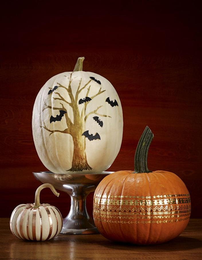 """<p>Use gold permanent marker to draw a tree on a tall white pumpkin. Add <a href=""""https://www.amazon.com/Heansun-Decals-Halloween-Sticker-Decor/dp/B07J4CH29J?tag=syn-yahoo-20&ascsubtag=%5Bartid%7C10070.g.1902%5Bsrc%7Cyahoo-us"""" rel=""""nofollow noopener"""" target=""""_blank"""" data-ylk=""""slk:bat stickers"""" class=""""link rapid-noclick-resp"""">bat stickers</a> and you're done! </p><p><a class=""""link rapid-noclick-resp"""" href=""""https://www.amazon.com/Sharpie-Oil-Based-Marker-Resistant-3-Pack/dp/B00FLJIMSM/?tag=syn-yahoo-20&ascsubtag=%5Bartid%7C10070.g.1902%5Bsrc%7Cyahoo-us"""" rel=""""nofollow noopener"""" target=""""_blank"""" data-ylk=""""slk:SHOP GOLD PAINT PENS"""">SHOP GOLD PAINT PENS</a></p>"""