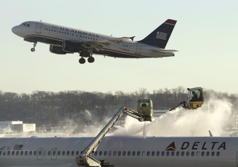 A Delta jetliner (bottom) is de-iced while a US Airways jet takes off at Reagan National Airport in Washington January 3, 2014. A heavy snowstorm and dangerously cold conditions gripped the northeastern United States on Friday, delaying flights, paralyzing road travel and closing schools and government offices across the region. REUTERS/Gary Cameron (UNITED STATES - Tags: ENVIRONMENT TRANSPORT TRAVEL)