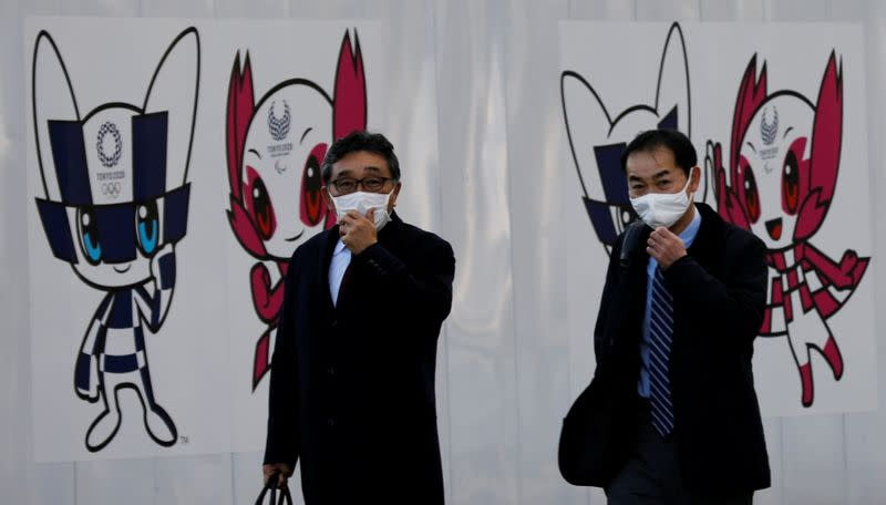 Men wearing protective face masks walk in front of a wall decoration featuring Tokyo 2020 Olympic Games mascot Miraitowa and Paralympic mascot Someity, amid the coronavirus disease (COVID-19) outbreak in Tokyo