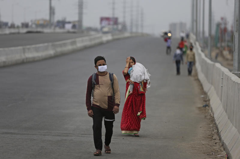 In this Thursday, March 26, 2020, file photo, an Indian couple carrying an infant walk along an expressway hoping to reach their home, hundreds of miles away, as the city comes under lockdown in Ghaziabad, on the outskirts of New Delhi, India. Over the past week, India's migrant workers - the mainstay of the country's labor force - spilled out of big cities that have been shuttered due to the coronavirus and returned to their villages, sparking fears that the virus could spread to the countryside. It was an exodus unlike anything seen in India since the 1947 Partition, when British colothe subcontinent, with the 21-day lockdown leaving millions of migrants with no choice but to return to their home villages. (AP Photo/Altaf Qadri, File)