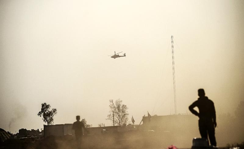 A helicopter prowls the perimeter of the Qayyarah military base, about 35 miles south of Mosul in Iraq on October 18, 2016 during an operation by Iraqi government forces-lead and US-supported efforts to retake the city from the Islamic State